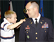 Lt. Col. Don Nestor smiles as his son carefully positions the shoulder strap with the silver oak leaf for the office of lieutenant colonel on his uniform during Nestor's promotion ceremony.