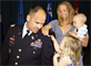 Lt. Col. Don Nestor leans over to make it easier for his daughter to position the lieutenant colonel rank insignia shoulder strap on his uniform as his wife, holding their infant son, helps.