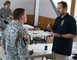 Spc. Timothy Steely, a current Operation Warfighter participant, speaks with Charles Case from the Defense Criminal Investigation Service, during a meeting held in July 2012. During the meeting, the Corps of Engineers spoke to other agencies about the program and how they can become involved.